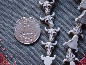 Teenie tiny unglazed porcelain ceramic bull skull bead
