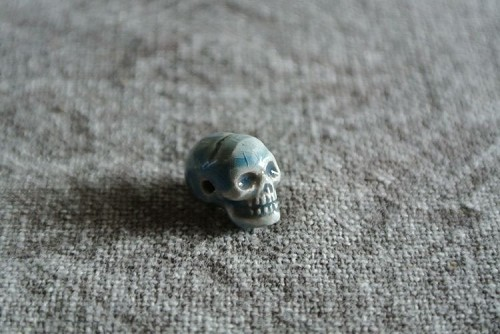 Teenie tiny porcelain ceramic skull bead with raku glaze.